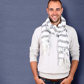 Modelo veste moletom cinza claro, calça jeans, e echarpe listrada em branco e cinza.