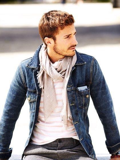 Modelo usa echarpe com jaqueta jeans e camisa branca listrada sutilmente em cinza.