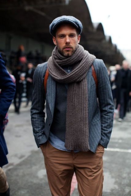 Modelo usa cachecol cinza, blazer azul e calça marrom.