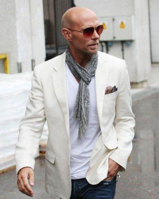 Modelo veste echarpe cinza, com blazer branco e calça jeans.