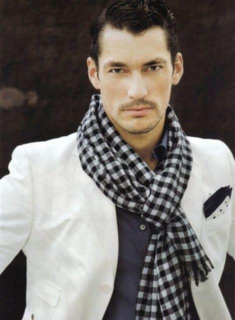 Modelo veste echarpe preto e branco xadrez, com blazer branco e camisa azul marinho por baixo.