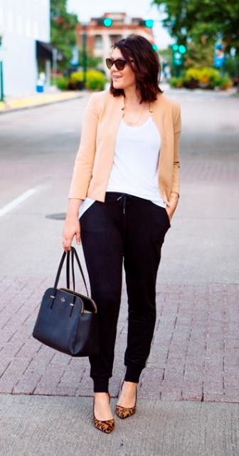 Modelo usa calça, sapatilha de onça, bolsa preta, blusa branca e casaco na cor bege claro.