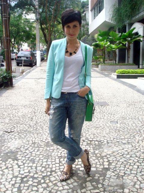 Modelo usa calça jeans, blusa branca, sapatilha de estampa de oncinha, blazzer verde agua e bolsa de ombro verde .