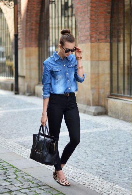 Modelo usa calça preta, bolsa no mesmo tom e camisa jeans azul.
