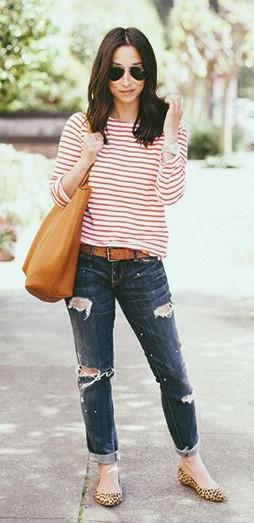 Modelo usa calça jeans azul escura destroyed,, blusa com listras em branco e vermelho, sapatilha de onça.