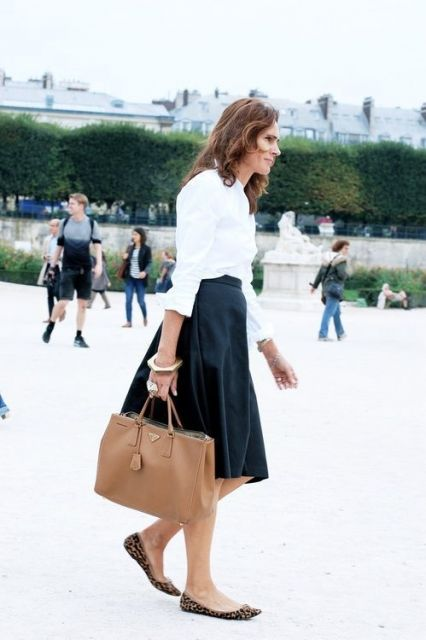 Modelo usa saia midi rodada azul, bolsa de mao bege, blusa branca e sapatilha estampa de onça.