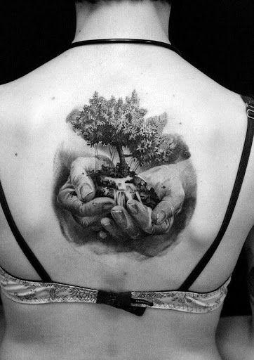 tatuagem de árvore da vida sendo segurado por duas mãos