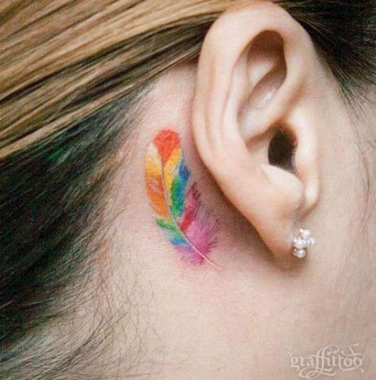 Modelo com tatuagem de pena colorida em tons de laranja, rosa, verde e azul.