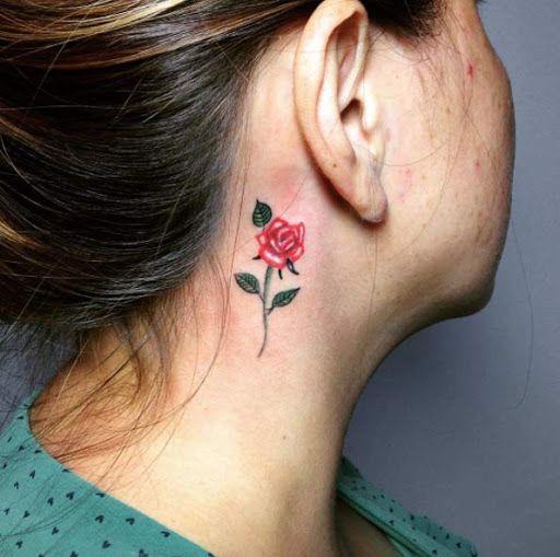 Modelo com tatuagem de rosa vermelha atras da orelha.
