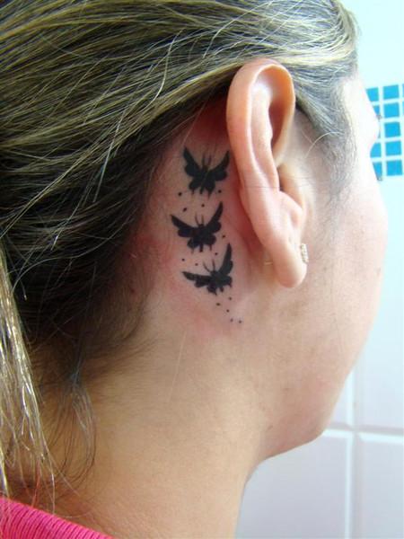 Modelo com três borboletas maiores, em tons de preto, atrás da orelha.