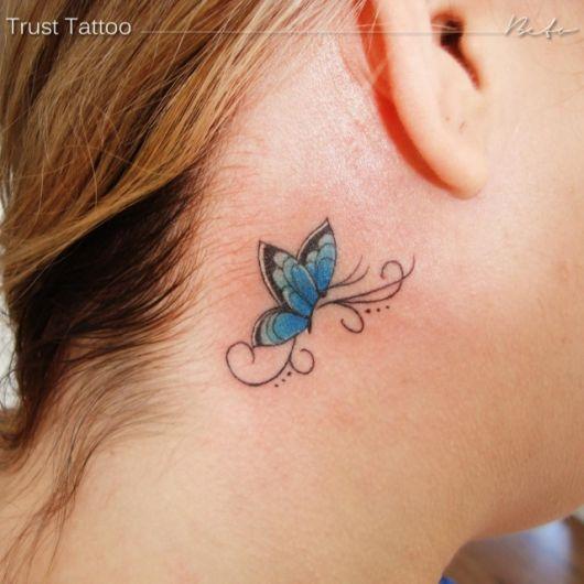 Modelo com tatuagem de borboleta atrás da orelha em tom de azul.