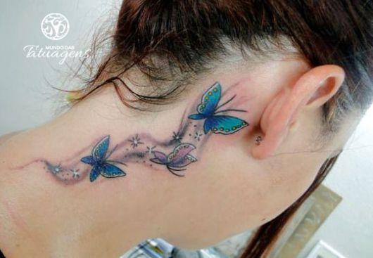 Tatuagem de três borboletas azuis, atrás da orelha.