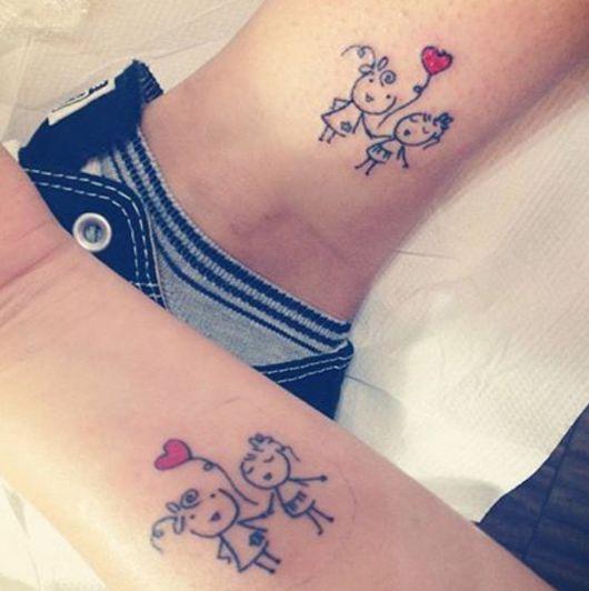 Modelo de tatuagem com duas bonequinhas e um coração.