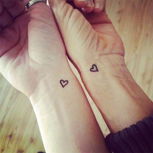 Tatuagem pequena de coração em punho.
