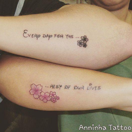 Modelo de tatuagem escrita, no braço com detalhes de flores preto e cor de rosa.