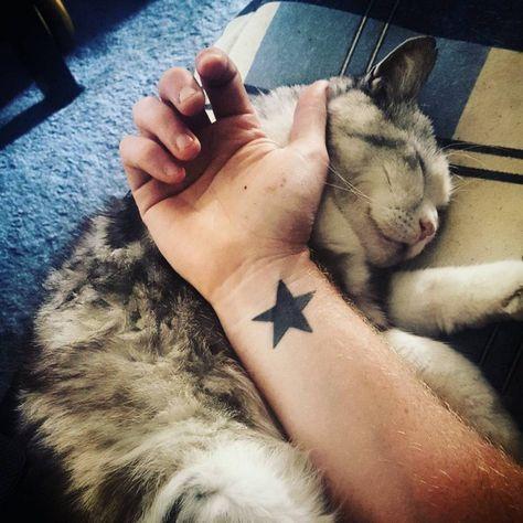 tatuagem de estrela pintada de preto no pulso