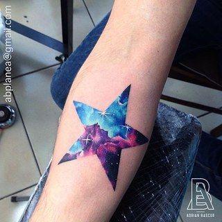 tatuagem de estrela com estampa colorida no braço