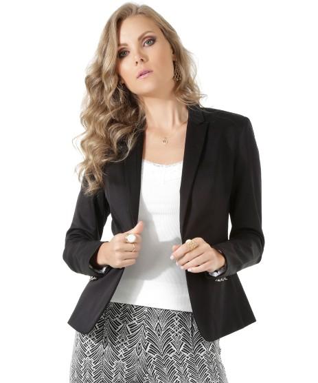 Modelo usa blusa branca, saia estampada e blazer preto de alfaiataria.