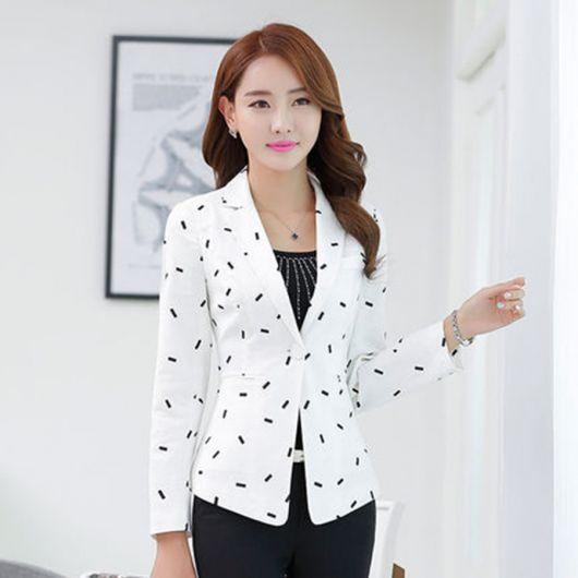 Modelo usa blazer branco com detalhes em preto, com vestido em tom de preto também.