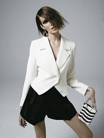 Modelo usa Blazer branco fechado, short preto e bolsa de mao carteira listrada de preto e branco.