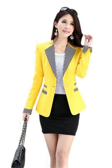 Modelo usa saia preta, blusa branca, bolsa preta, blazer amarelo.