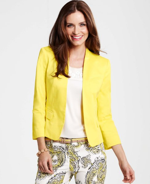 Modelo usa calça estampada, blusa branca com blazer amarelo.