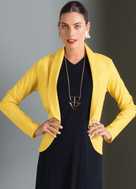 Modelo usa vestido preto, com blazer amarelo e colar dourado.