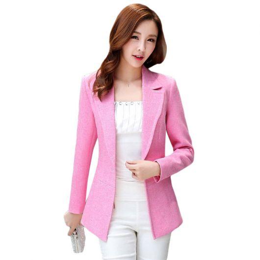 Modelo usa calça branca, blusa branca, blazer rosa.