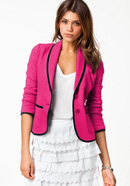 Modelo usa blazer rosa com preto, saia de babdo branco e blusa de alcinha.