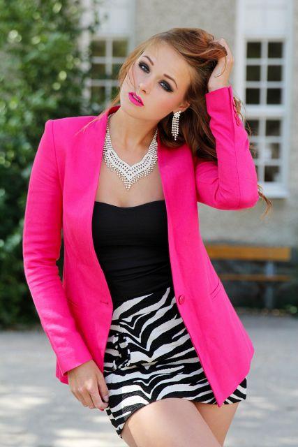 Modelo usa blusa preta, saia estampada em preto e branco e blazer rosa vivo.