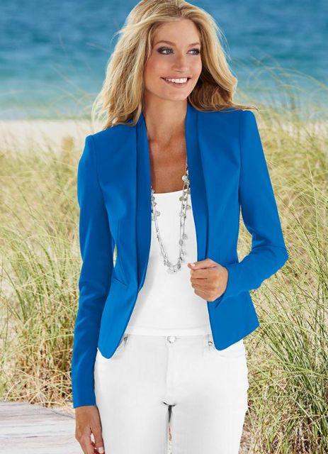 Modelo usa calça branca, blusa branca, colar longo e blazer azul.