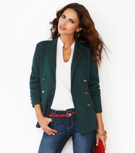 Modelo usa blazer verde escuro, calça jeans e blusa branca.