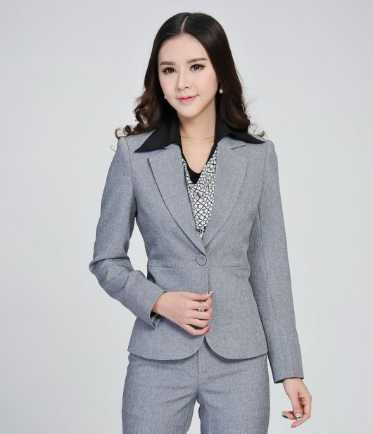 Modelo usa blazer cinza e calça no mesmo tom com colar .
