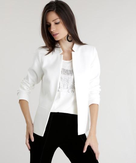 Modelo veste blazer off white, calça preta e blusa branca.
