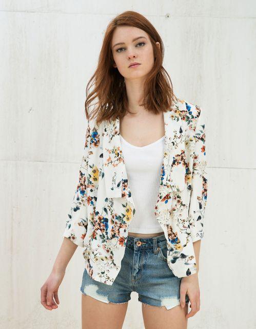Modelo usa look com bermuda jeans, blusa branca e blazer estampado.