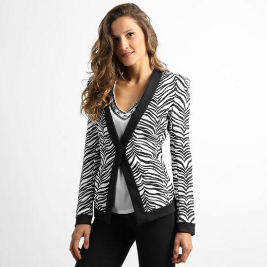 Modelo usa blazer animal print de zebra, calça preta e blusa branca.