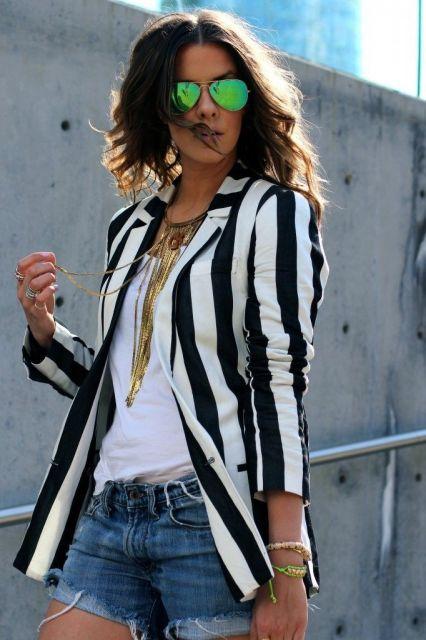 Modelo veste bermuda jeans, blusa branca e blazer listrado em preto e branco.