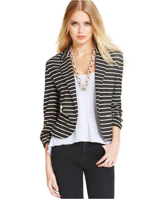 Modelo usa calça preta, blusa branca e blazer listrado com listras finas e horizontais.