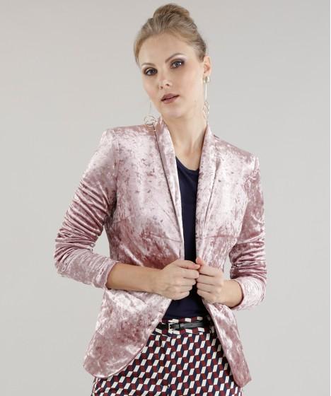 Modelo usa saia estampada, blusa preta e blazer rosê.