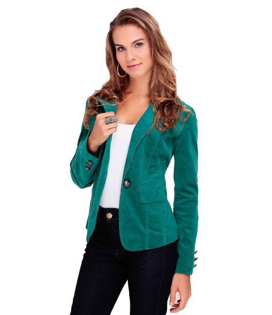Modelo usa calça preta, blusa branca e blazer verde.