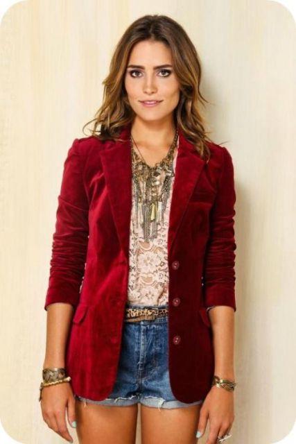 Modelo usa short jeans, blusa estampada e blazer vermelho.