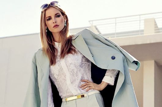 Modelo usa blusa branca e blazer azul claro.