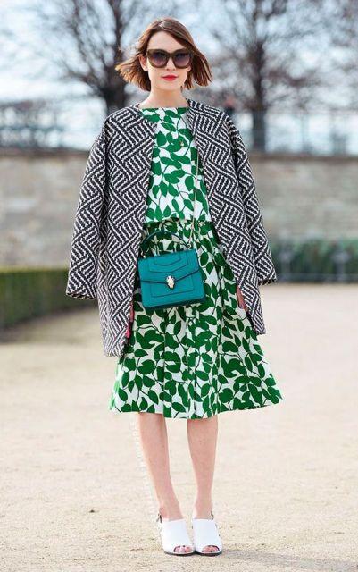 Modelo veste vestido verde estampado, blazer estampado em preto e branco, tenis branco e bolsa transversal verde.