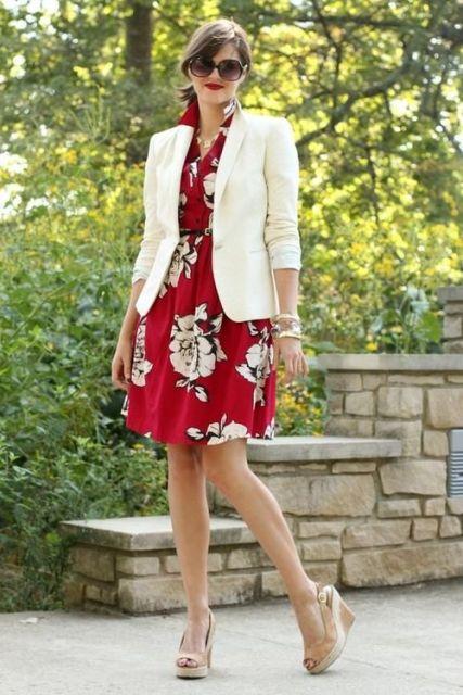 Modelo usavestido vermelho estampado, blazer branco e sandalia de salto.