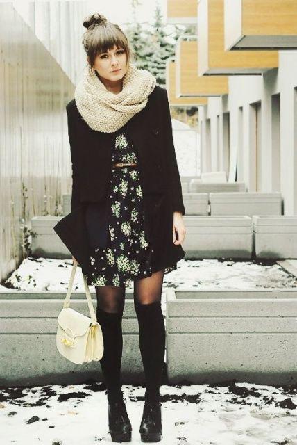 Modelo usa vestido preto floral, blazer preto, bolsa creme e botas pretas cano longo.
