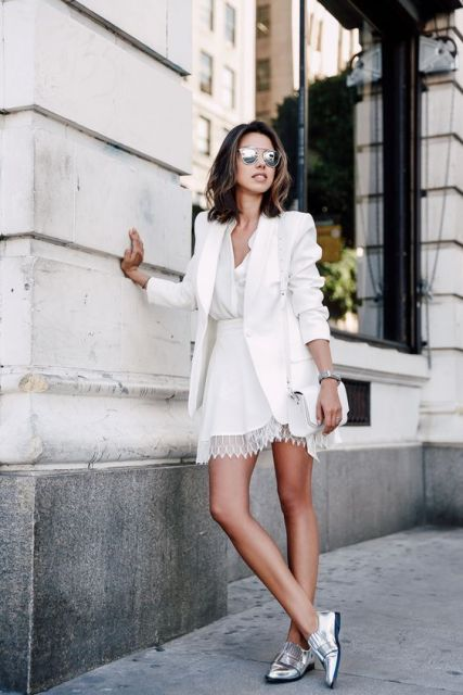 Modelo usa vestido branco e blazer no mesmo tom com sapato metalizado.