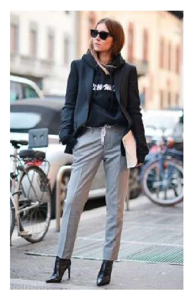 Modelo veste calça cinza, bota preta, blazer e moletom preto.