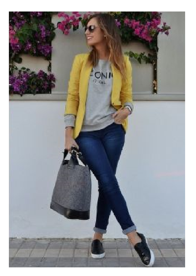 Modelo veste calça jeans, sapato preto e branco , moletom cinza, blazer amarelo