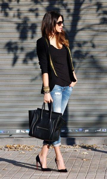 Modelo veste calça jeans, sapato preto, blazer blusa e bolsa no mesmo tom.