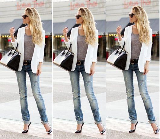 Modelo usa calça jeans,sapato preto, bolsa no mesmo tom, blusa fininha cinza.´e blazer branco.